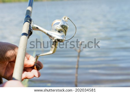Fisherman using a spinning reel for freshwater fishing on a rural lake, close up of his hands and the reel - stock photo