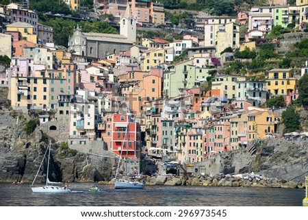 Fisherman village Riomaggiore is one of five famous colorful villages of Cinque Terre in Italy, suspended between sea and land on sheer cliffs - stock photo