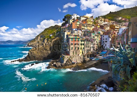 Fisherman village  Riomaggiore is one of five famous colorful villages of Cinque Terre in Italy, suspended between sea and land on sheer cliffs upon the  turquoise sea. - stock photo