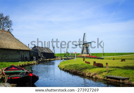 Fisherman village with canal, windmill, boat and traditional Dutch houses.  - stock photo