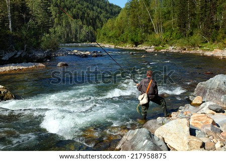fisherman with a rod on the mountain's river - stock photo