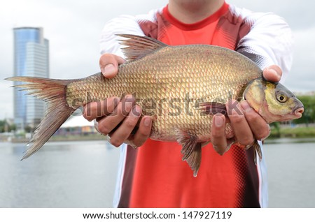 Fisherman with big bream holding in arms - stock photo