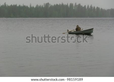fisherman with boat rain and fog - stock photo