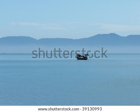 Fisherman with his small boat in a misty morning - stock photo