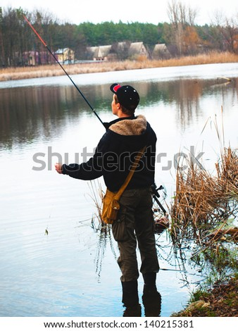 Fisherman with spinning in the evening on the lake - stock photo