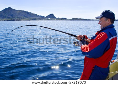 Fisherman with spinning on the boat near the Lofoten island - stock photo