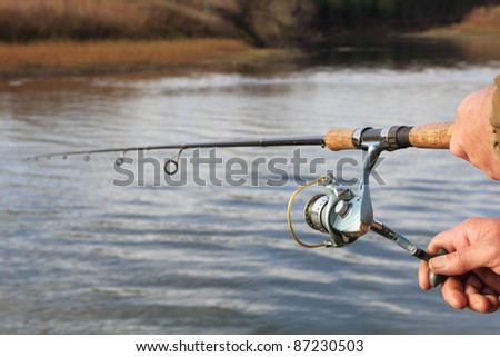 Fisherman with spinning on the river - stock photo