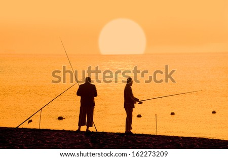 Fishermans silhouette at sunrise - stock photo