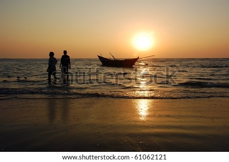 Fishermen are walking away from the fishing boat at the end of the working day at sunset in the Indian state of Goa. - stock photo