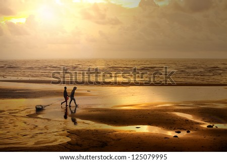 Fishermen at dawn sky background with sun rays and reflected in the sea water - stock photo