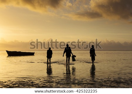 Fishermen coming from ocean on traditional fishing boat in Zanzibar at sunrise