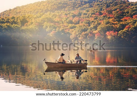 fishermen fishing in a lake in the early morning - stock photo