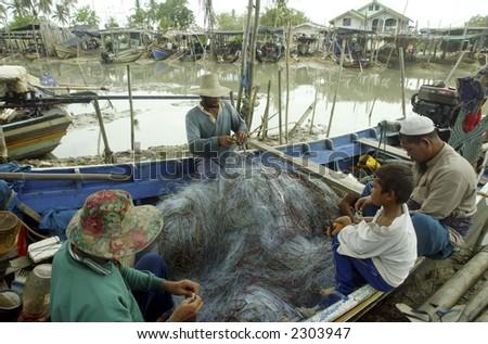 Fishermen fix fishing nets. - stock photo
