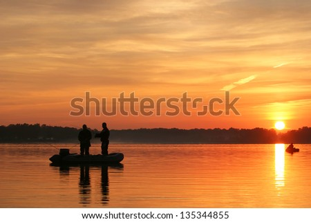 fishermen go fishing from a boat at sunrise - stock photo