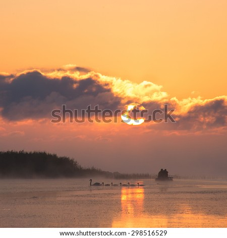 Fishermen in a boat at dawn - stock photo