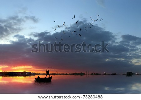 Fishermen in a boat at sunset - stock photo