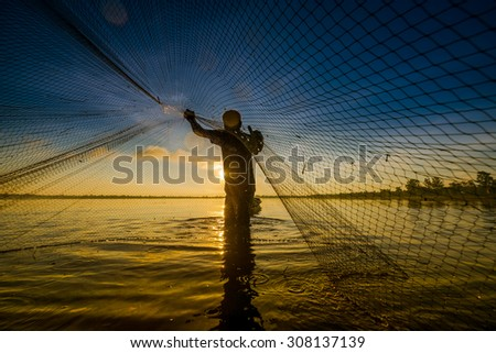 Fishermen in action when fishing in the lake , Thailand - stock photo