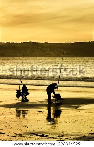 fishermen in  the beach  with orange sky  at dusk in atlantic coast - stock photo
