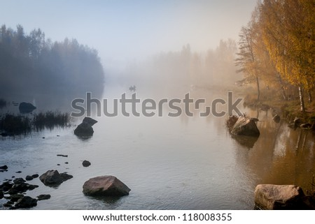 Fishermen in the boat on the river in autumn - stock photo
