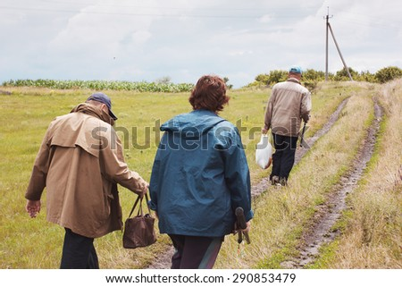 Fishermen in village. Three people return home from fishing trip. Rural landscape with road