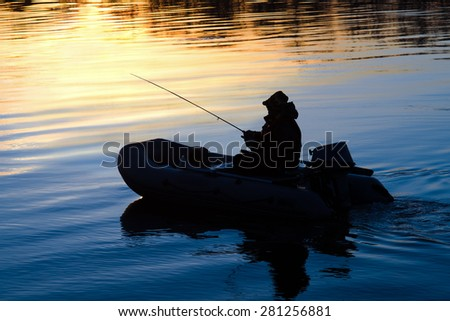 Fishermen on a boat with a fishing rod on the river at sunset - stock photo