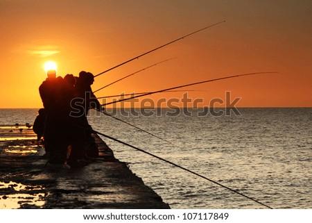 Fishermen on sunrise on the pier - stock photo