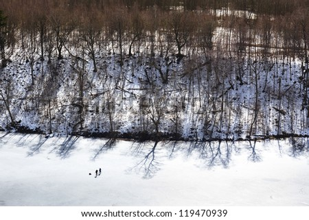 Fishermen on the surface of  frozen lake, Lithuania - stock photo