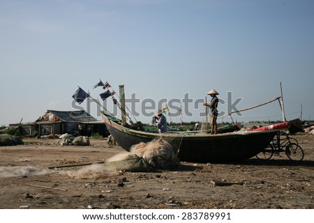Fishermen repairing nets on a boat trip out to sea in the afternoon July 31, 2014 at the beach of Hai Ly, Vietnam.