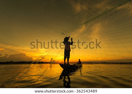 Fishermen silhouette lifestyle in action when fishing in the river, Thailand