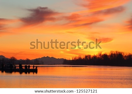 Fishermen, Steveston Harbor Sunrise. Fishermen line up on the floating dock in Steveston trying their luck at sunrise. Richmond, British Columbia, Canada. - stock photo