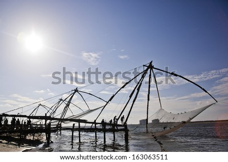 Fishermen with Chinese fishing nets at a harbor, Cochin, Kerala, India