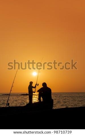 fishermens at sunset - stock photo