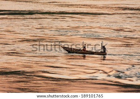 Fishers in boat rows against evening glow reflection in Victoria Nile River background at sunset. Jinja, Uganda, Eastern Africa.  - stock photo