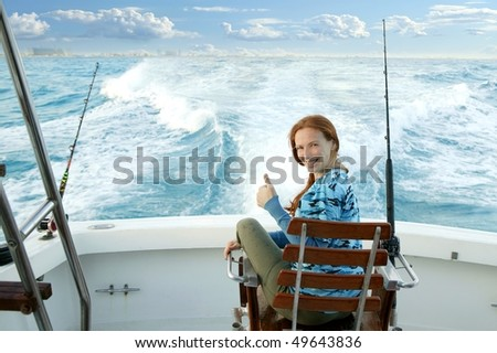 fisherwoman big game on boat chair ok sign happy - stock photo