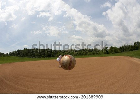 Fisheye view of a baseball apparently hovering in mid air with female pitcher in the background. - stock photo