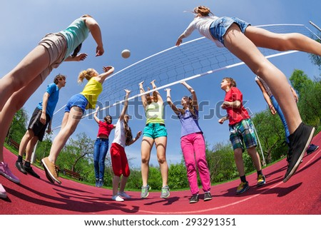 Fisheye view of teens playing volleyball outside - stock photo