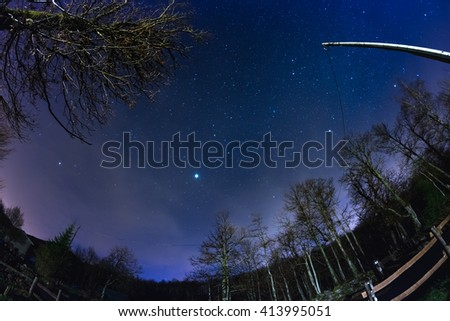 Fisheye view of the starry sky with blurred motion clouds, captured from sparse beech woodland. Jupiter and Lion constellation in the center. Scenic distortion and 180 degree view. - stock photo