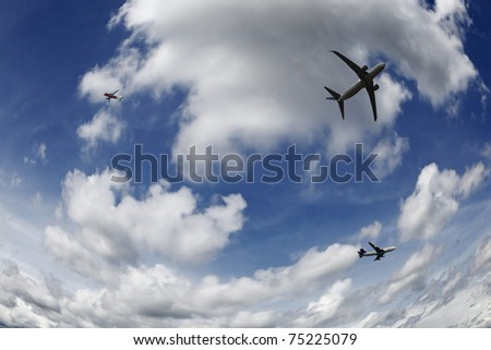 Fisheye view of three airplane soaring through a serene blue cloudy sky. - stock photo