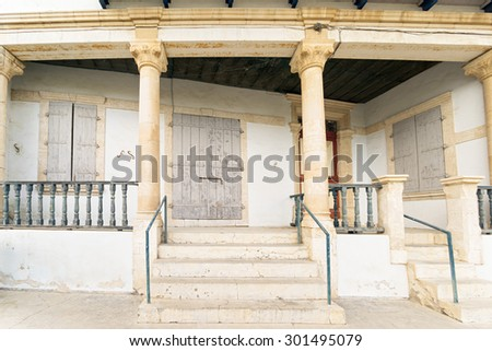 Fisheye view on old mansion with closed door and windows,  column, stairway and rails. Pano Lefkara, Cyprus.