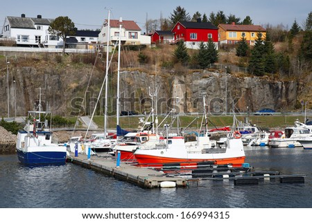 Fishing and pleasure boats stand moored in Norway village - stock photo