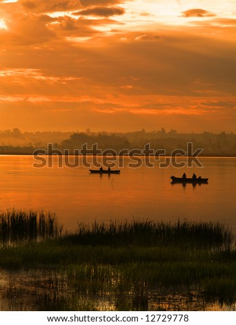 Fishing at dawn under an incredible orange sunrise - stock photo