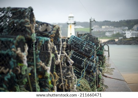 Fishing at St Ives harbor with a view past a stack of old wire lobster or crab traps to the lighthouse at the harbor entrance - stock photo