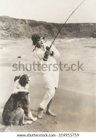 Fishing at the beach with her dog - stock photo