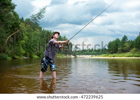 Fishing before the storm. A young man catches a fish on spinning, standing in the river. Wildlife and heavy storm clouds in the background