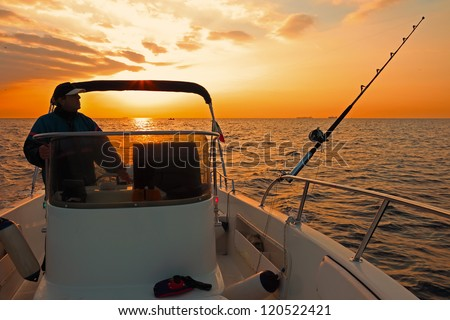 Fishing boat and fisherman in ocean at dawn - stock photo