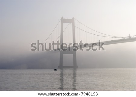 Fishing boat and grey suspension bridge in background – Foggy day by Little Belt in Denmark