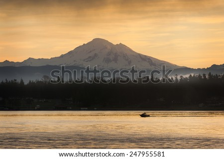Fishing Boat and Mt. Baker. A sport fishing boat cruises past Mt. Baker in the Cascade Mountain range at sunrise in the Puget Sound area of western Washington state. - stock photo