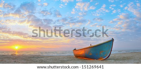 Fishing boat and sunrise on Black Sea beach - stock photo