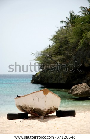 Fishing boat at a white beach in Curacao - stock photo