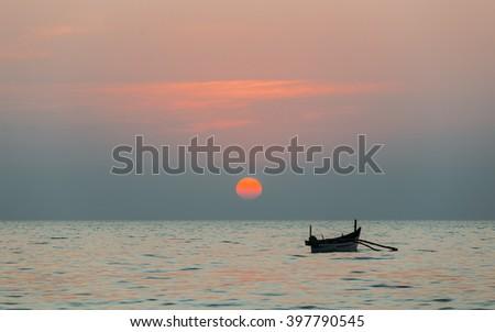Fishing boat at sunset. Goa, India. - stock photo